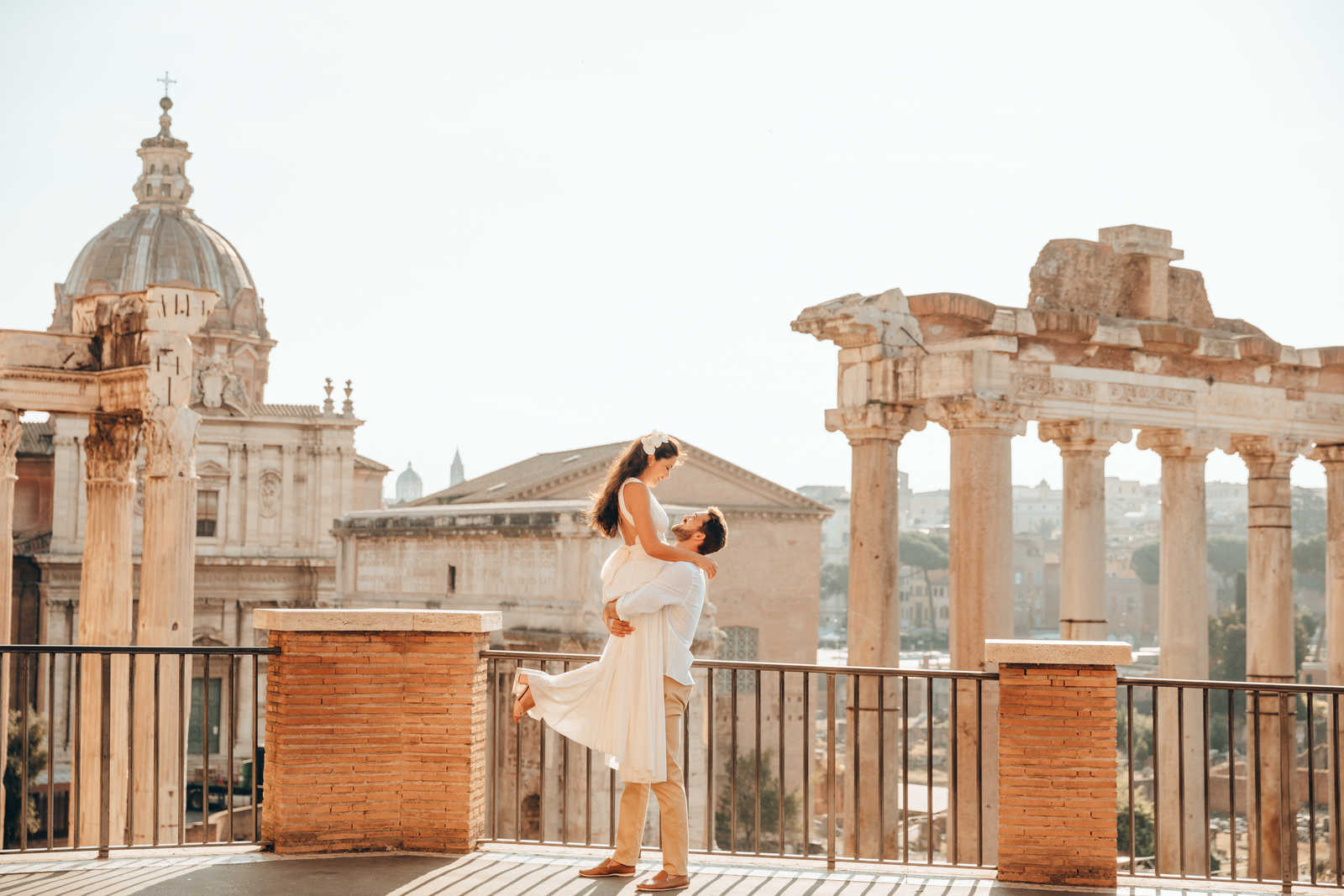 Noivo levantando a noiva em frente das Ruínas do Fórum Romano.