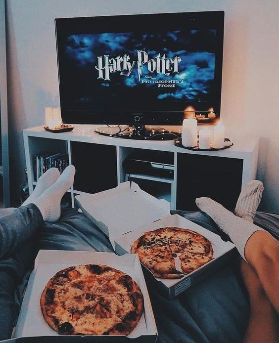 Casal sentado na cama, apenas as pernas aparecendo, com duas pizzas sobre a cama e a tv ligada com o filme do Harry Potter.
