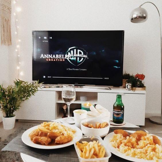 Mesa de centro, com batata frita, frango frito e taça de vinho e tv ao fundo com o logo da WB.
