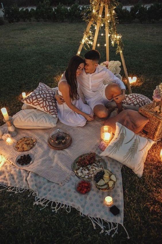 Casal sentado sob uma toalha branca em cima da grama, com almofadas em volta, com luzes de led e vela iluminando, com comidas para fondue.