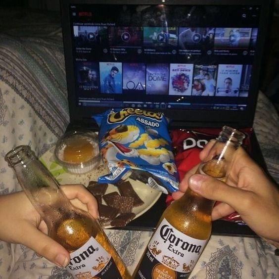 Casal deitados, brincando duas cervejas da marca Corona, com salgadinhos sobre o Notebook ligado com Netflix.