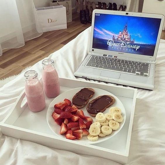 Bandeja branca sobre a cama, com um prato com panquecas, banana e morango cortado, dois copos com vitaminas de morango ao lado e o notebook a frente com o logo da disney.
