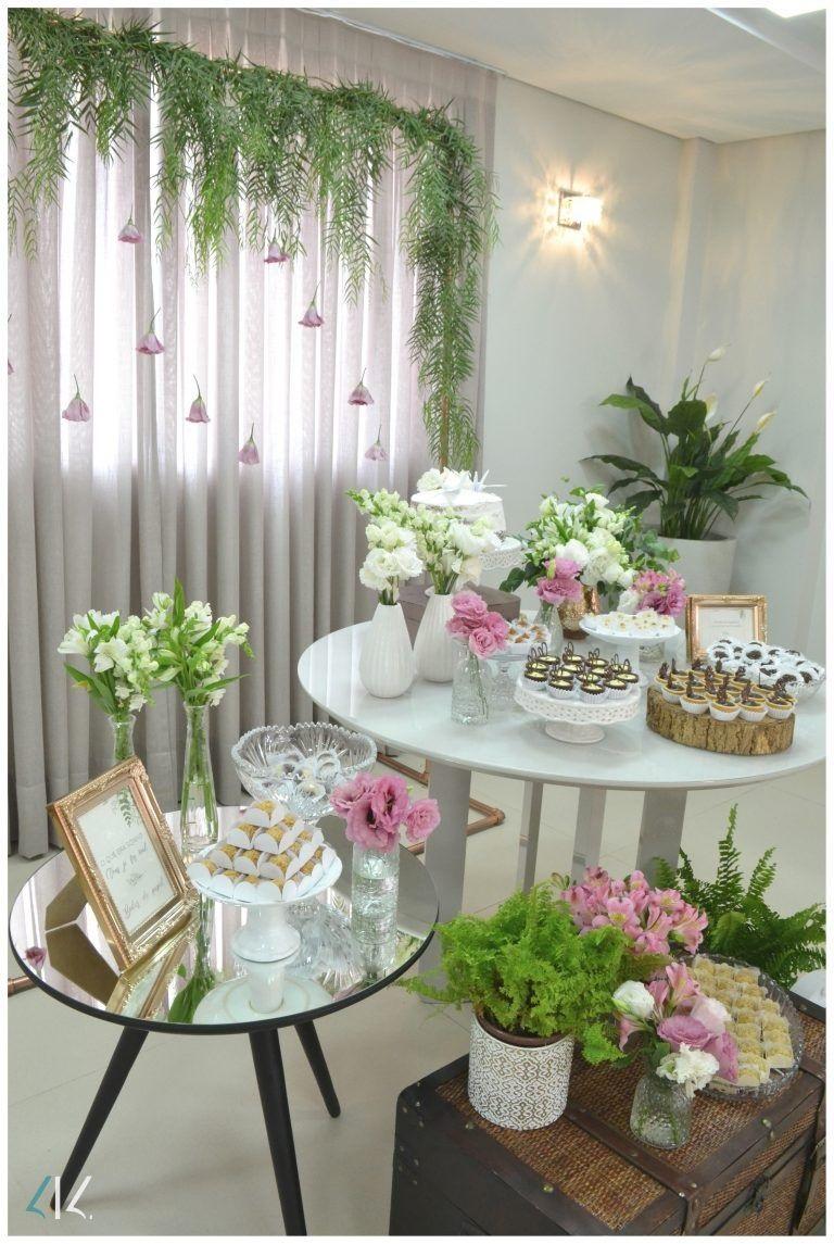 Duas mesas pequenas, decoradas com docinhos e vasos de vidro transparente com flores brancas e rosas. Cortina branca no fundo, com folhas verdes e flores rosas. Baú a frente das mesas com mais plantinhas e flores brancas e rosas.