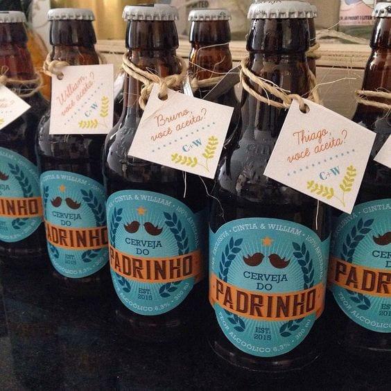Cerveja de garrafa, com rotulo de Cerveja do Padrinho em azul e uma tag com o nome do padrinho amarrada com barbante.