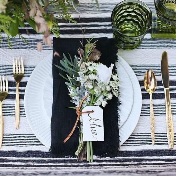 Mesa posta com pano branco com listras pretas, talheres dourados, pratos brancos, com um guardanapo preto e flores do campo por cima.