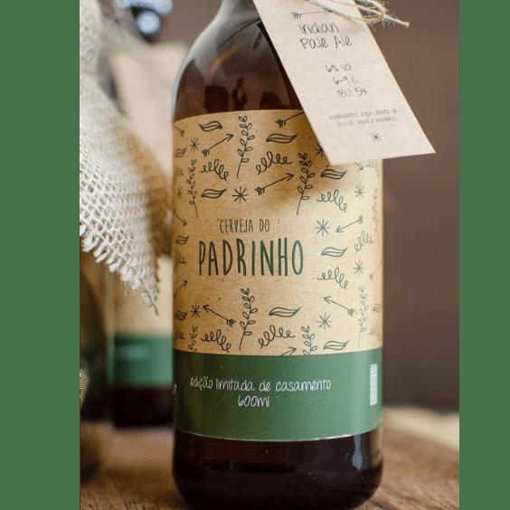 Cerveja de garrafa, com rotulo de Cerveja do Padrinho em papel reciclável e verde e uma tag com o nome do padrinho amarrada com barbante.