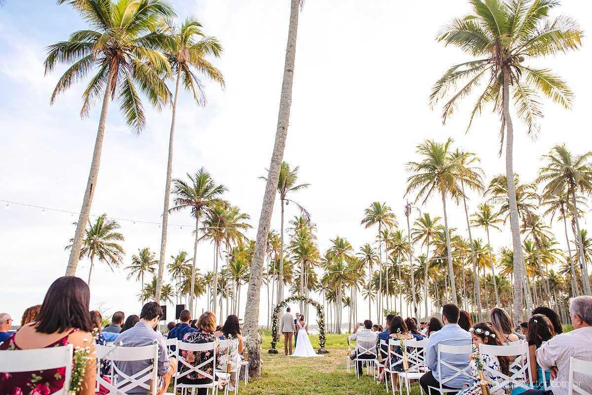 Convidados sentados em cadeiras brancas, noivos sendo casados com coqueiros a volta.