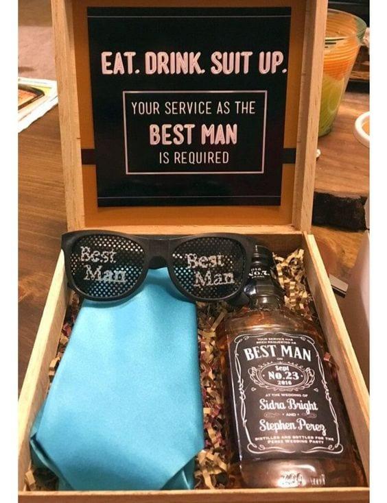 Caixa de madeira, com gravata verde tifany, garrafa pequena de Jack Daniels, com logotipo de Best Man e nome dos noivos.