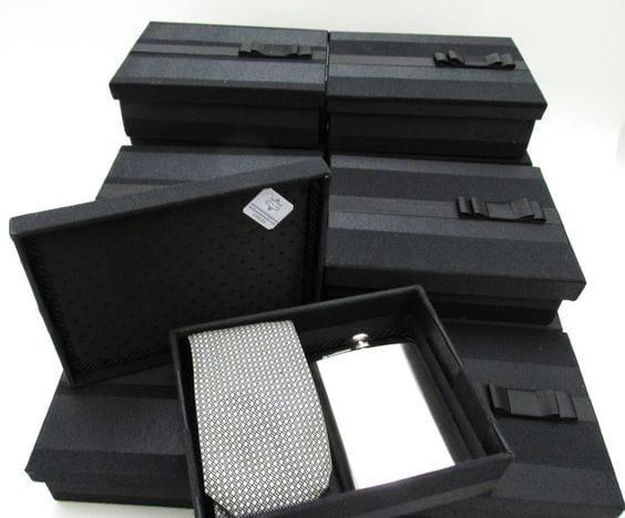 Caixa preta contendo um cantil para bebida em prata e uma gravata cinza com pontos brancos.