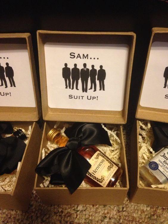 Caixa MDF com garrafa de whisky com uma gratava borboleta por cima e na dentro da tampa da caixa, o nome do padrinho com a frase Vista-se (referência a séria How I Meet Your Mother).