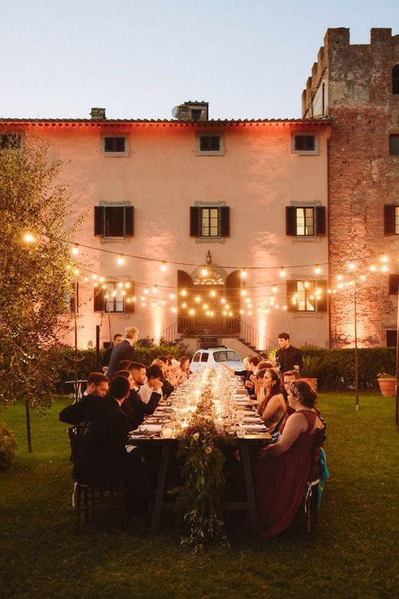 Mesa com convidados em volta realizando jantar no campo, e luzes de led iluminando.