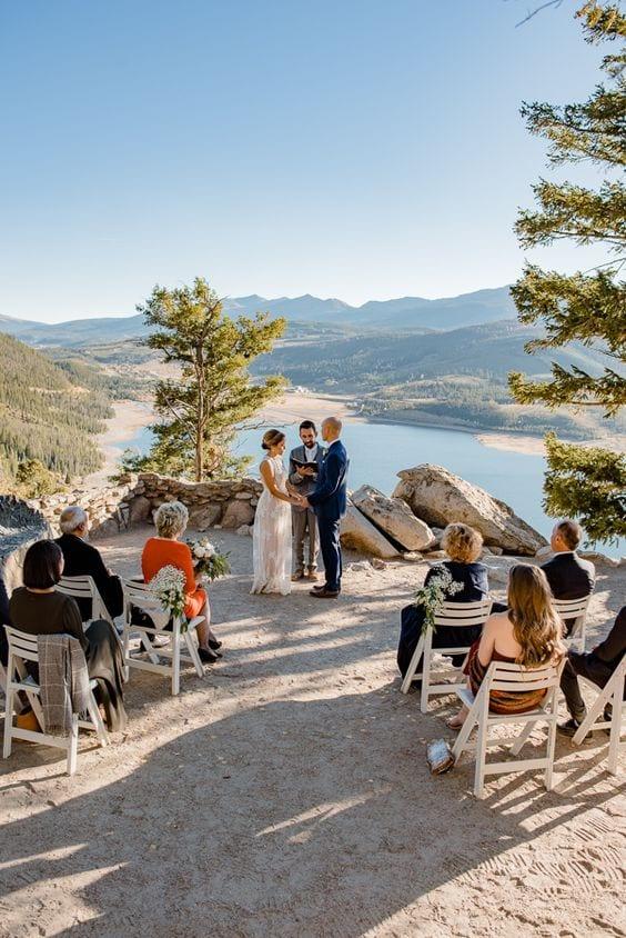 Casamento sendo realizado em uma montanha, com vista para o rio, com alguns poucos convidados sentados em cadeiras brancas.