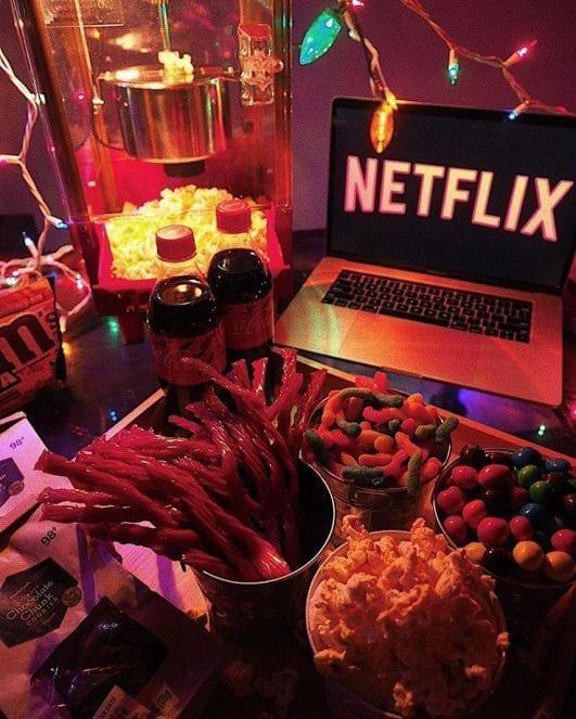 Fini, Pipoca e outros snacks sobre a mesa, com coca cola e m&m a esquerda, e notebook com a tela da Netflix.