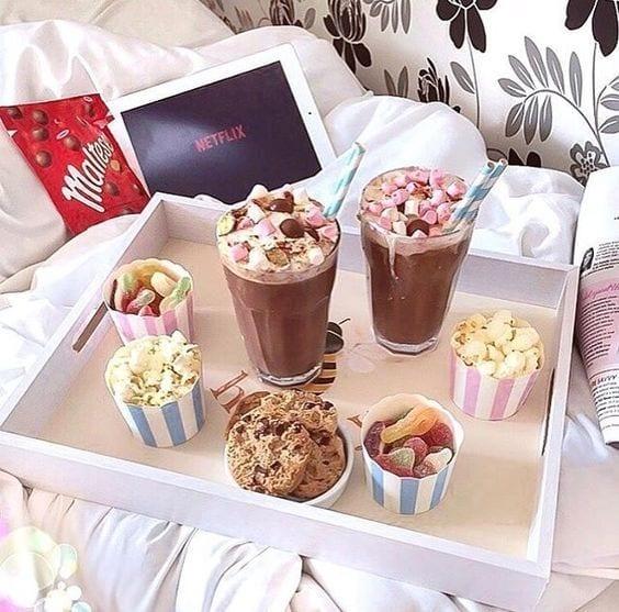 Bandeja branca para comer na cama, com milkshake, pipoca, cookies e notebook atrás com Netflix.