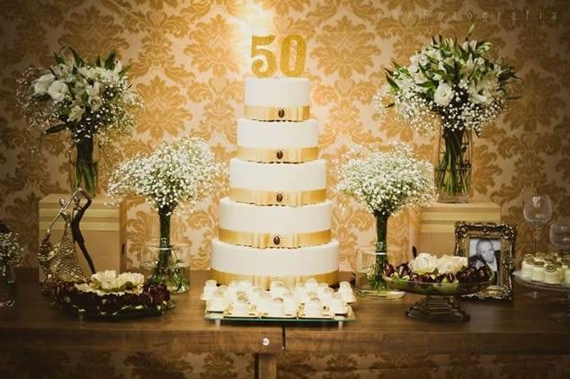 Mesa retangular de madeira marrom, papel de parede bege com dourado, vasos de flores de vidro transparente e flores brancas, bolo de altares em branco e fitas douradas com topo de 50 anos em dourado.