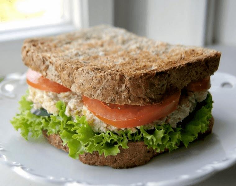Lanche integral de frango, com alface, rúcula e tomate.