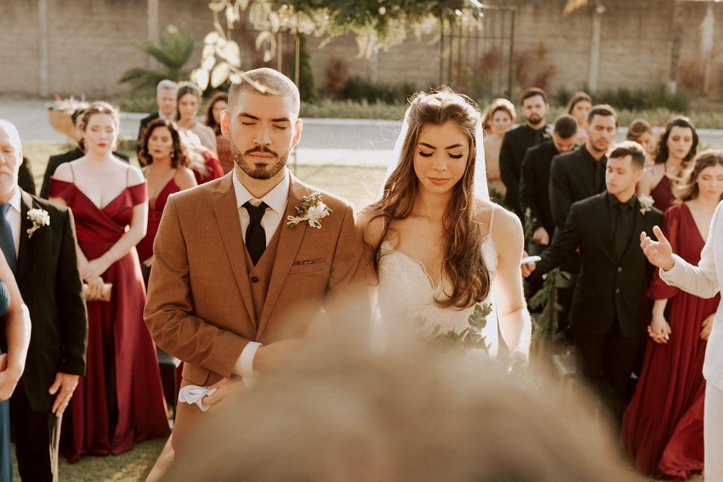 noivos juntos no altar , a noiva possui um buquê verde de rosas brancas
