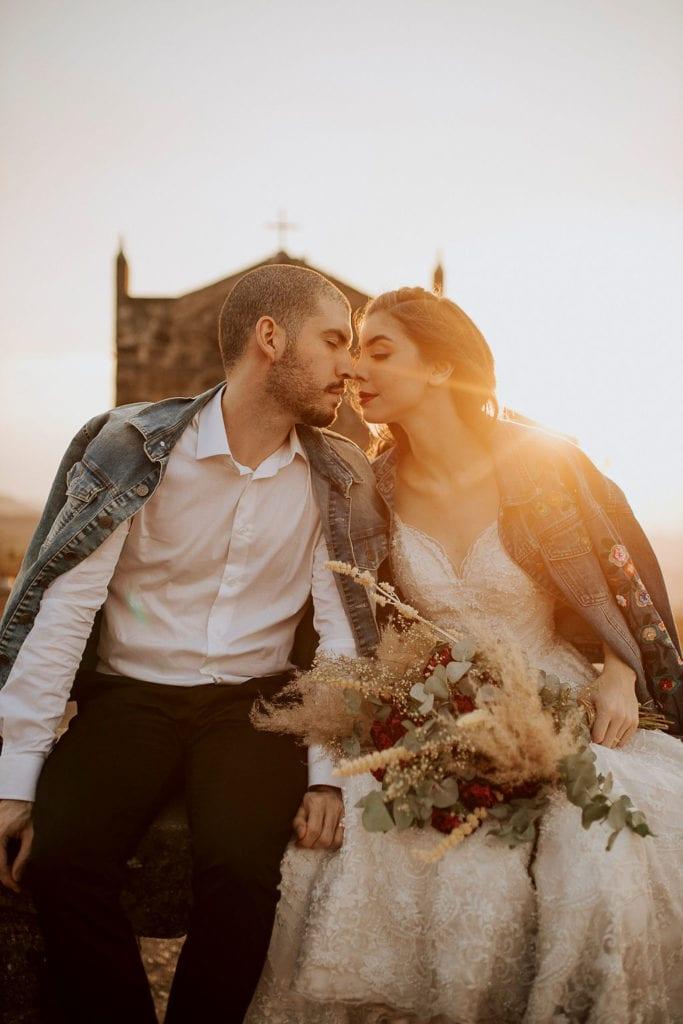 noivos posam no pôr do sol, a noiva usa uma jaqueta e um buquê de folhas secas - fotos pós wedding