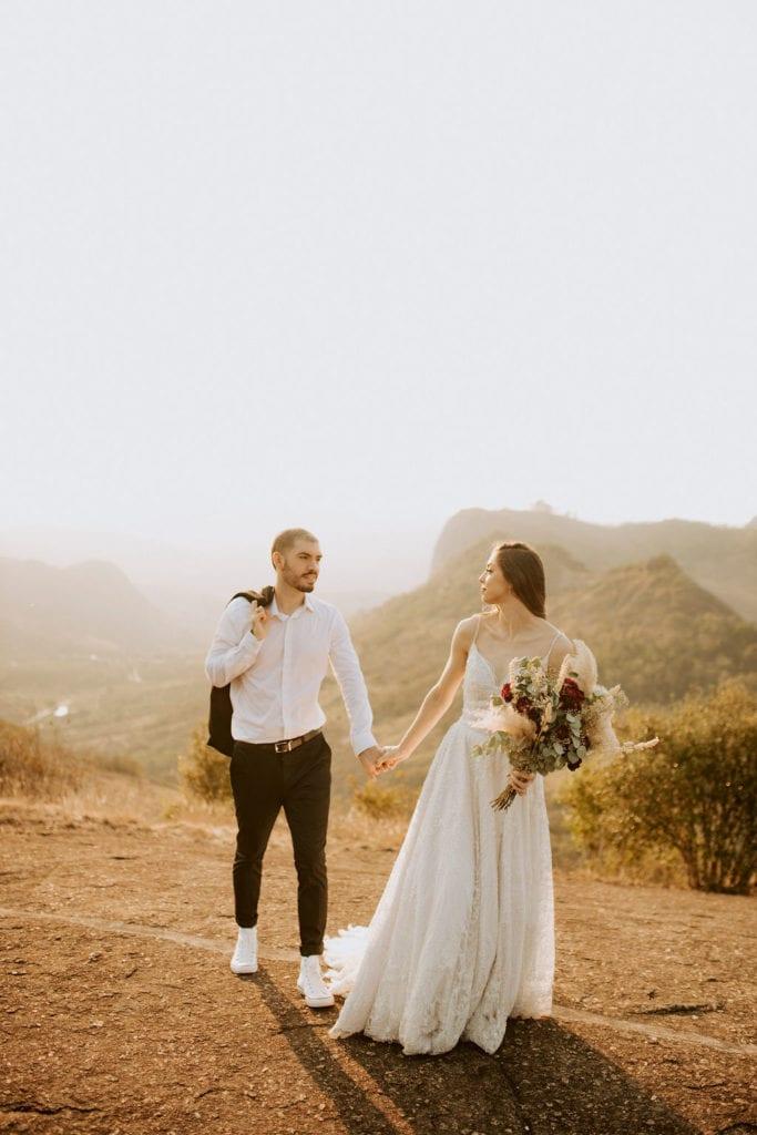 noivos posam no alto de um monte - fotos pós wedding