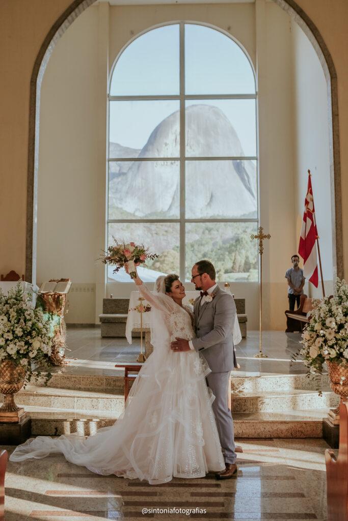 foto dos noivos ao final da celebração com pedra azul ao fundo