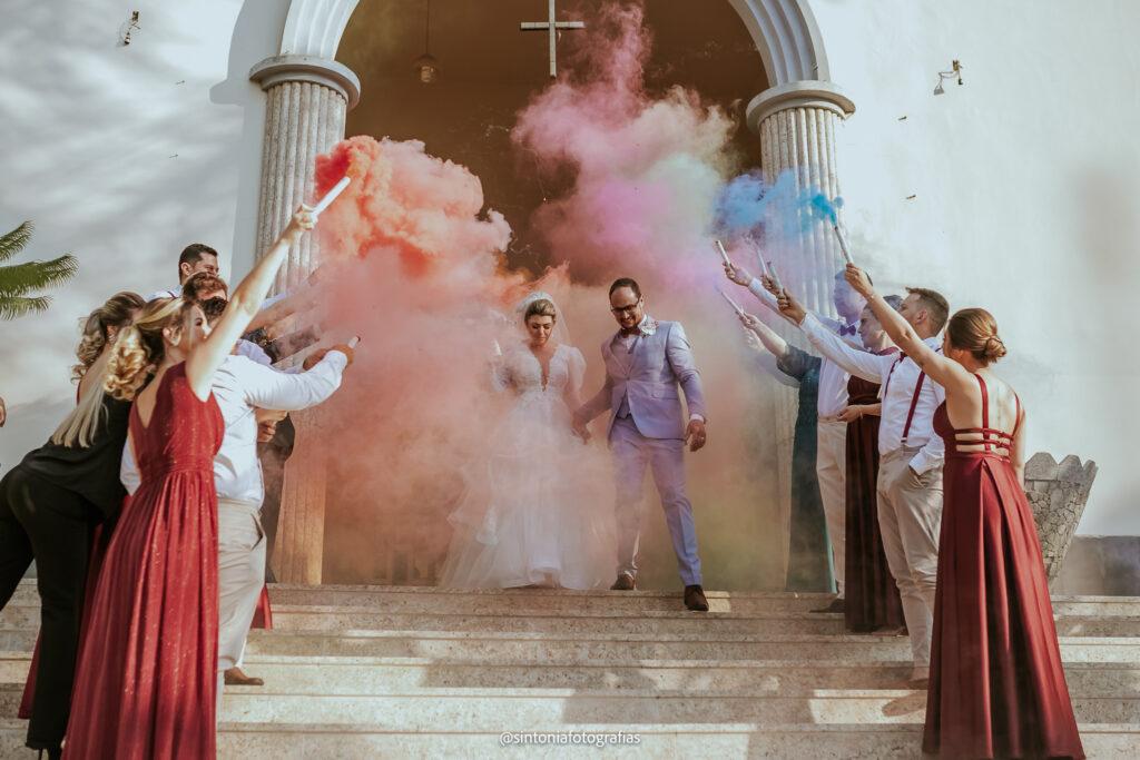 noivos saindo da igreja e sendo festejados pelos padrinhos